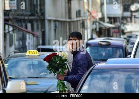 BAKU, AZERBAIJAN - MARCH 19 2014 A young man offers drivers the chance to buy flowers as they move slowly through - Stock Photo