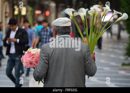 The flower seller in Fountain Square, Baku, capital of Azerbaijan. A man sells lilies to locals and tourists - Stock Photo