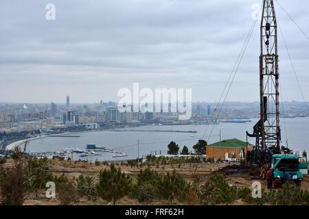 Oil drilling rig in Baku, capital of Azerbaijan, with view over the city and Caspian Sea. Drilling for oil near - Stock Photo