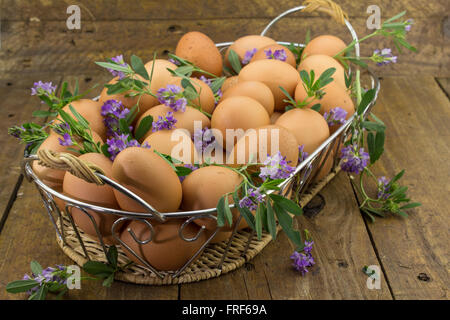 Photo of a clutch of eggs and wild flowers in a basket on rough wooden bench - Stock Photo