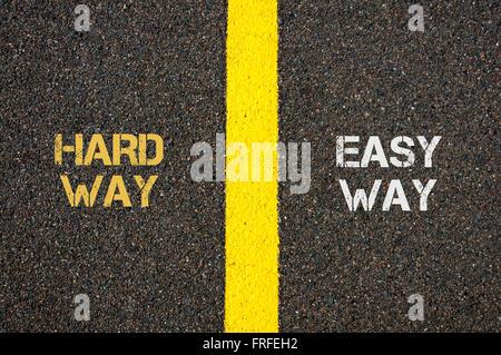 Antonym concept of HARD WAY versus EASY WAY written over tarmac, road marking yellow paint separating line between - Stock Photo