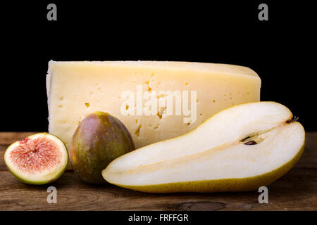 pear, cheese and fig on wood tasty appetizer black background - Stock Photo