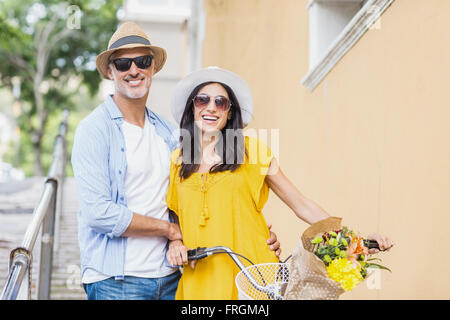 Portrait of happy couple with bicycle - Stock Photo