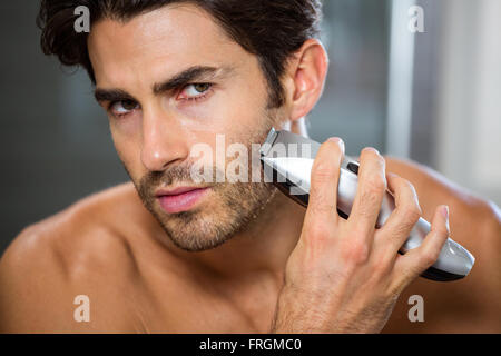 Man shaving with trimmer - Stock Photo