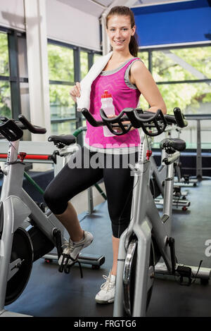 Woman standing beside exercise bike - Stock Photo
