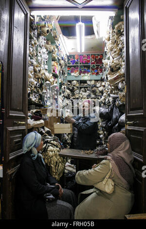 two Tunisian women at the doorsteps of a small shop full of clothes are served from the shops owner all of them - Stock Photo