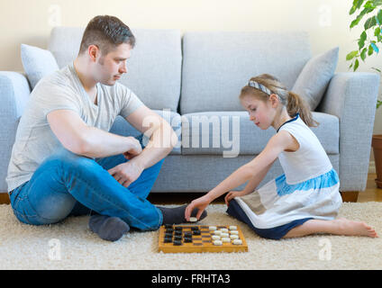 Little girl and her father playing checkers. - Stock Photo