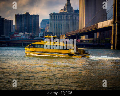 New York Water Taxi with Brooklyn Bridge on the East river, New York, USA - Stock Photo