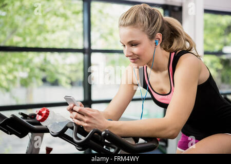 Woman listening music and text messaging - Stock Photo