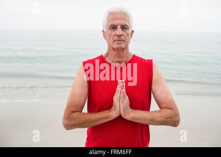 Portrait of senior man in lotus position - Stock Photo