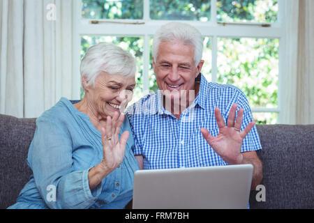 Smiling senior couple waving hand while using laptop - Stock Photo