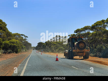 roadworks on a highway in Western Australia. Heavy machinery tractor paving gravel on a road side behind limiting - Stock Photo