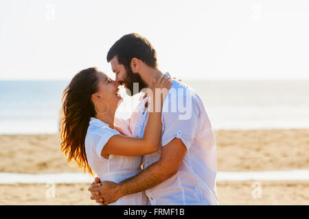Happy newlywed family on honeymoon holidays - just married loving man and woman embracing on sea sand beach. - Stock Photo