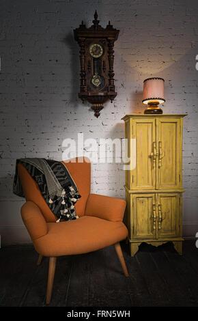 Still life of vintage orange armchair, yellow cupboard, wooden pendulum clock and illuminated table lamp on a wooden - Stock Photo