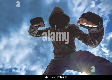 Violent attack, unrecognizable hooded male criminal kicking and punching victim on the street. - Stock Photo