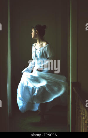 young woman dancing in an old house wearing white long romantic dress - Stock Photo