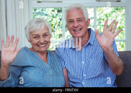 Portrait of happy senior couple waving hand - Stock Photo