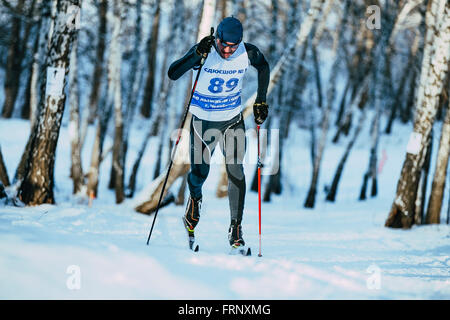 young male skier during race forest in classic style in Championship of Chelyabinsk in cross-country skiing - Stock Photo