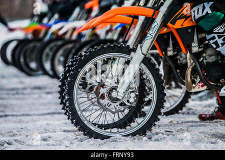 riders and wheels of motorcycles on starting line during Cup Winter motocross - Stock Photo