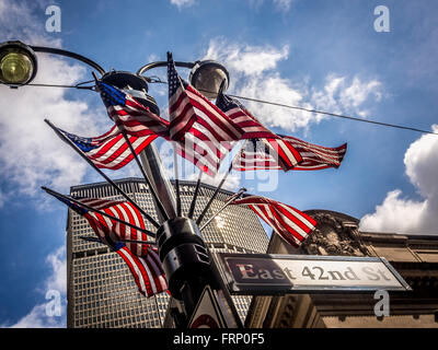 East 42nd St sign and group of American flags on lamppost, New York City, USA. - Stock Photo