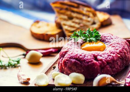 Raw beef .Tasty Steak tartare. Classic steak tartare on wooden board. Ingredients: Raw beef meat salt pepper egg - Stock Photo