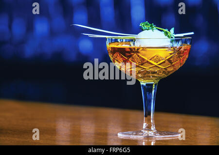 Alcoholic beverage based on bar counter with balls ice cubes - Stock Photo