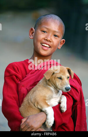 Portrait of a young Buddhist monk playing with a pet dog at a temple in Amarapura, Mandalay, Myanmar (Burma) - Stock Photo