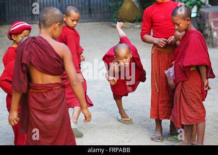 Young Buddhist monks playing at a temple in Amarapura, Mandalay, Myanmar (Burma) - Stock Photo