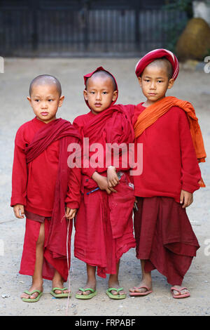 Three young Buddhist monks at a temple in Amarapura, Mandalay, Myanmar (Burma) - Stock Photo