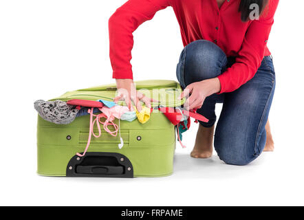 Hard to to pack overflowing suitcase. On a white background. - Stock Photo