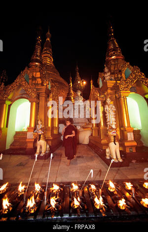 Monk walking in Temple,front of offerings candle.Mandalay Myanmar - Stock Photo