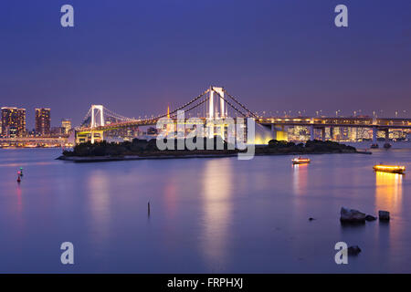Tokyo Rainbow Bridge over the Tokyo Bay in Tokyo, Japan. Photographed at night. - Stock Photo