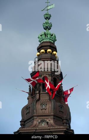 Copenhagen, Denmark, March 23rd, 2016. The Danish flag, Dannebrog,  on half on the Parliament spire in Copenhagen - Stock Photo