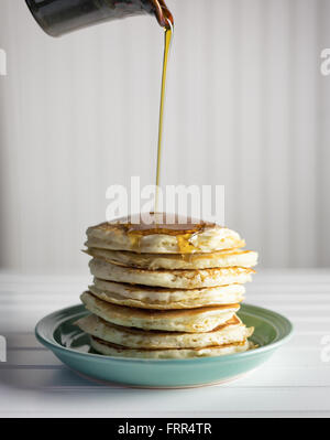 Maples syrup being poured over a tall stack of pancakes. - Stock Photo