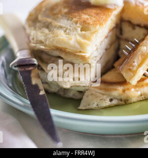 A small stack of sliced pancakes with butter and syrup. - Stock Photo