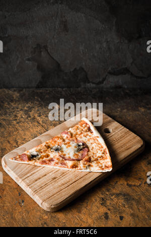 Slice of pizza on the wooden board vertical - Stock Photo