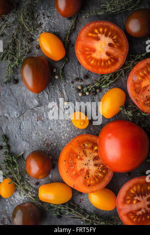 Tomatoes mix  with herbs on the stone table vertical - Stock Photo