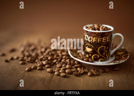 Cup full of coffee beans on the wooden background - Stock Photo