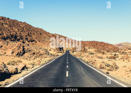abandoned highway in desert landscape - long straight road - vintage look - Stock Photo