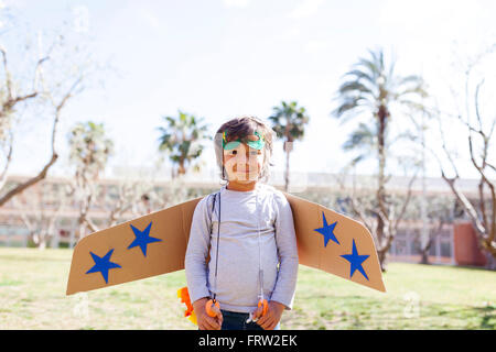 Portrait of happy little boy dressed up as a superhero standing on a meadow - Stock Photo