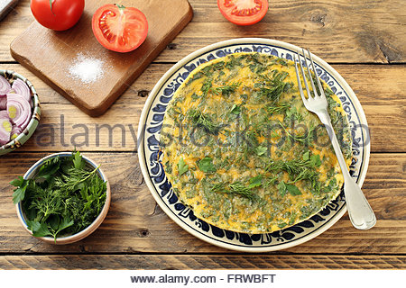 scrambled eggs with herbs in a detailed ceramic plate rustic background - Stock Photo