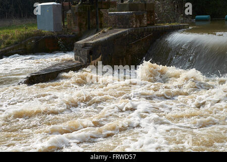 Floodwater flowing over a weir and gauging station on the River Great Ouse, Bedford, Bedfordshire, United Kingdom. - Stock Photo