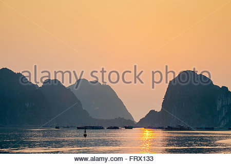 Sunset over karst mountains in Ha Long Bay, Quang Ninh Province, Vietnam - Stock Photo
