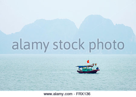 Small fishing boat in Ha Long bay on a foggy day, Quang Ninh Province, Vietnam Stock Photo