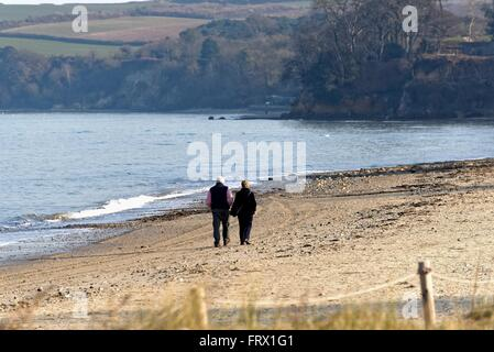 Elderly couple walking on a deserted beach at Studland Bay Dorset UK - Stock Photo
