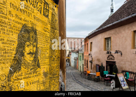 Sighisoara, Romania - March 12, 2016: Vlad Tepes portrait and a cobblestone alley in Sighisoara, Romania - Stock Photo