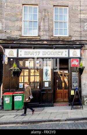 A young woman walking past the Brass Monkey pub in Edinburgh. - Stock Photo