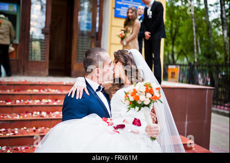Newlywed couple being showered in rose petals, groom hold his bride on hands - Stock Photo