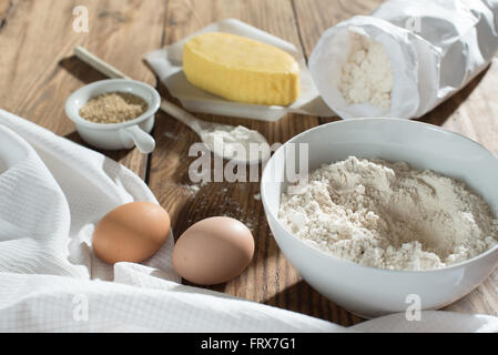 ingredients to make a cake on a wooden table, a bowl flour, sugar, butter, eggs and napkin - Stock Photo