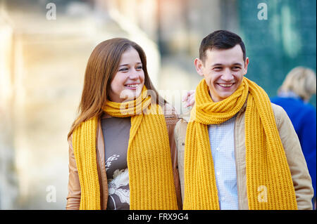Cheerful couple walking through the city together - Stock Photo